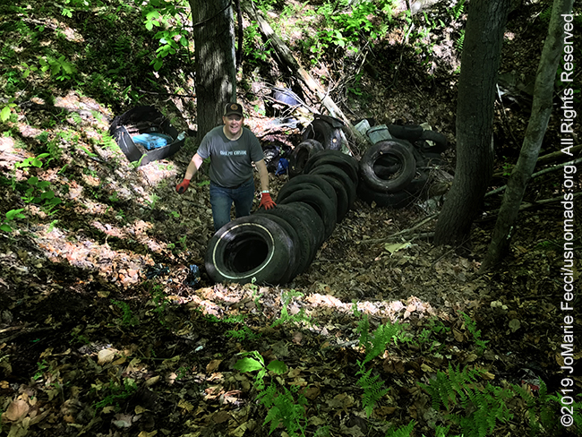 PA_May2019_0511_TrailCleanup_volunteerwithpileoftires-crop_IMG_6443_650w